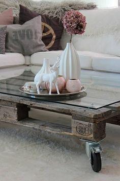 table basse en palettes avec fleurs et canapé blanc avec coussins colorés