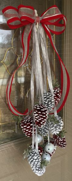 Pine cone door wreath with painted red and silver snow dipped pine cones with silver bells.