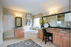 Gehan Homes Master Bathroom - Light wood cabinet, brushed nickel hardware, gray rug, vanity, corner drop in tub. Houston, Texas   Westover Park Classic - Georgetown #Gehanhomes