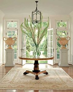 dramatic and airy foyer - dreamy!  oriental rug, pedestal table, lantern pendant