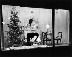 """McCurdy & Co. department store window in downtown Rochester; A tree and fireplace scene with children looking up the chimney. A banner proclaims """"Christmas: Keep it Shining For All the World."""" c.1940"""