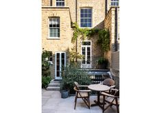 Petit but perfectly formed chelsea garden with raised balcony, french doors leading out to a garden paved in york stone.