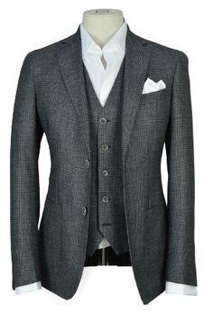 Ce micro carreau, dans un camaïeu de gris, donne au tissu du relief et de la modernité. Veste 2 boutons, col tailleur à large revers, poches plaquées pour une allure plus casual, complétée par un gilet 5 boutons.