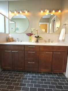 Rich cherry wood cabinets warm the space and charcoal slate tile grounds the floor in this clean and simple bathroom design.