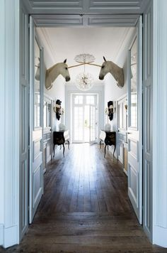 """Château de Goujeonnerie: In the entrance hall, a pair of """"unicorns"""" (or stuffed white horse heads affixed with horns) add a whimsical touch to the fairytale space. Entry Hall, Home And Deco, Vintage Modern, Modern Victorian, Decoration, My Dream Home, Interior And Exterior, Chandeliers, Living Spaces"""
