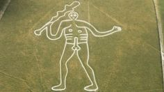 Looking down on the naked chalk figure of the Cerne Giant on the grassy hill