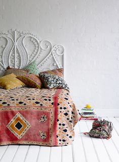 Create a white space. Then decorate with interesting textiles in a mixture of patterns and colors. Keep them touching and confined in a space. This creates a visual painting with the elements of the room. - Rebecca Rebouche