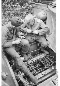 Two panzer crewmen working on their Tiger's engine. June 1943.