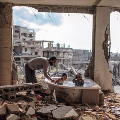 @emadsnassar _June 26, 2015. Salem Saoody, 30, bathing his Daughter Layan (L) and his Niece Shaymaa (R) in the only remaining Piece of their damaged House. They now live in a Caravan near the rubbles. photo By @emadsnassar _@everydaymiddleeast # gaza