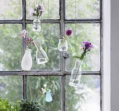 Love this! Hanging vases. Wrap several small, lightweight containers and vases at the neck or a notch with a fixed string or wire and tie.