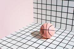 basket ball laying on a black and white grid, next to pastel pink wall. Graphic…