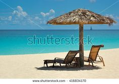 Thatch umbrella and chaise longe on a beautiful beach in Anguilla - stock photo