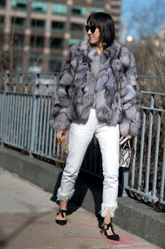 A fur coat paired with fringe jeans.