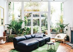 Parisian apartment of Jean-Christophe Aumas with blck leather sofa and green plants. Black Leather Sofas, Black Sofa, Vintage Chairs, Vintage Furniture, Bored At Home, Parisian Apartment, Scandinavian Home, Elle Decor, Home Decor Accessories
