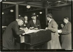 Interpreter and recorder interviewing newcomers, Ellis Island, New York, 1908. (Lewis W. Hine)