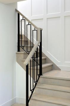 Your daily dose of Inspiration: A gray wash wood staircase is finished with hollow iron balusters alongside a staircase wall clad in wainscoting. Stair Railing Design, Iron Stair Railing, Iron Balusters, Staircase Railings, Staircases, Banisters, Staircase Walls, Staircase Molding, Metal Stair Railing