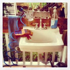 Gardeners need a handy space and it's awfully convenient for kids too!  Use the faucet hose adapter from the hardware store and water all the porch plants.  Fresh water connected to the outdoor spigot via a washer hose and the drain pipe taps into the gutter takeaway drain.  It works!