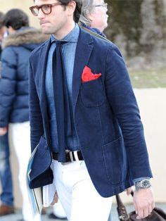 Denim shirt, navy blazer, red pocket square, white pants, big stones.