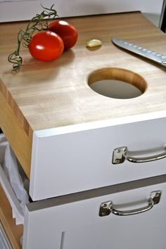 Built in cutting board above garbage. Makes a lot of sense! -- above compost bucket would be better.