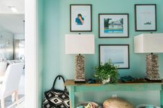 An old farm table with faded wood on top and distressed teal paint on the legs was cut in half long ways and affixed to the wall, to create the mudroom console table. The table provides a place to rest keys, sunglasses and other daily essentials.