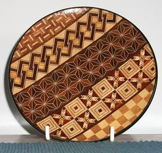 A small dish or saucer from Japan, which has amazingly intricate patterns created using different kinds of wood, in a style commonly called Yosegi. The dish measures 14cms and is signed on the underside. It comes with its original box and dates possibly from the 1960/70s. Two