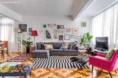 Sala de estar com sofá cinza, tapete p&b e quadros e objetos com toques de cor.