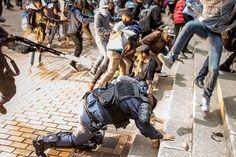 Johannesburg, Sudafrica Il bagliore dello scoppio di una granata stordente mentre uno studente dell'università di Witwatersrand sta per saltare su un poliziotto a terra e un altro poliziotto spara dal suo fucile con munizioni in gomma, in scontri durante una protesta degli studenti contro le tasse universitarie