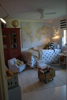 Boys room: Crate on casters for stuffed animal storage, large red armoire for clothing, large map and globe, striped curtains, navy and white striped fabric headboard