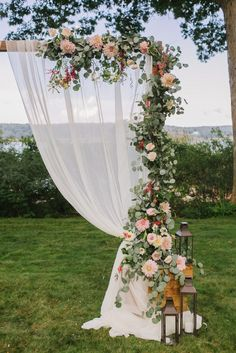Romantic Ceremony arbor with fabric and eucalyptus garland and cafe au lait dahlias and roses. Blush Floral design. Photo by Emily Tebbetts