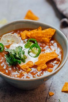 Bowl of chicken enchilada soup made in the Instant Pot topped with sour cream, cilantro, sliced jalapenos, tortilla chips and a lime wedge