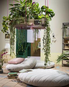 Un salón con tres cojines de suelo grandes con fundas de color beige; encima de los cojines, un estante colgante con plantas.