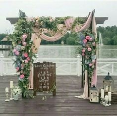 Ceremony arch with elaborate draping and flowers in dusty pink