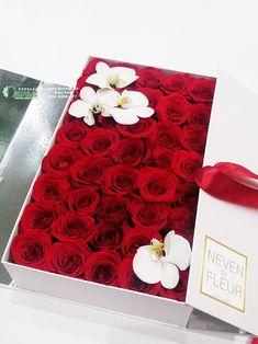 Ruže i cvetovi orhideje ''Phalaenopsis'' u izduženoj kutiji.