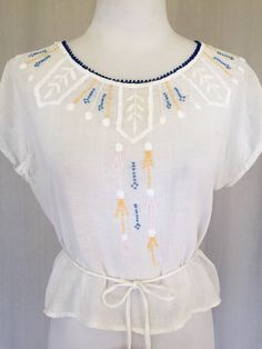 Gorgeous 1920s loose weave cotton, semi sheer blouse with yellow, blue, soft pink and white art deco embroidery around entire neckline and front center of blouse. Cap sleeves, back hook and eye closure and attached tie belt at back waist. Blouse is in good, wearable condition but is delicate for its age and has a a repair at right arm pit, and one at bottom back right of top near where the belt is attached. Both are more visible when top is off or on close inspection * please note- item is…