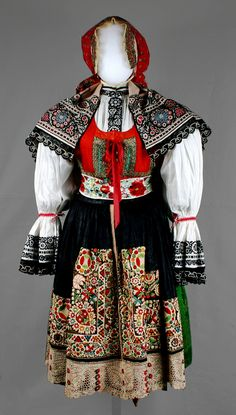 Moravian folk costume, 1900-1925  Gift of Mrs. Olga Dana (1957.168-.170f)    This costume came to Wisconsin from Kyjov, Moravia, where folk costumes were symbols of national pride and of opposition to Germanization in the nineteenth century. Moravians took great pride in their embroidery. Women spent long nights throughout the year working on these elaborate pieces of art. Often created as part of dowries, embroidered dresses became family heirlooms as they were passed from generation to…