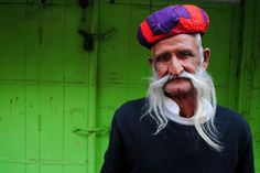 This is street photograph of an old man having an extended mustache