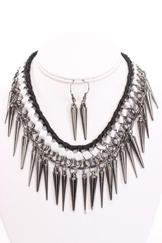 Create curiosity in all you pass when you add a prick of glamour to your sleek ensemble and peep toe platform pumps, with this spiky necklace. Its adjustable chain link necklace is uniquely structured, while its spiked pendents with two tone ribbon wrapped accents spur excitement in similarly edgy fashionistas. Laying gently over your collar bone, add an extra bit of excitement to todays ensemble by adding whats sure to be your new fave accessory. Pair with the matching metallic plastic ...
