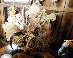 """thrift store basket, pampas grass """"feathers"""", dry/silk flower arranging block (to stick stuff into), chicken feathers, will last years"""