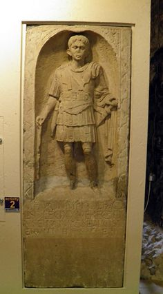 Here is Marcus Favonius Facilis, a Roman army officer of Legion XX.  Originally his tombstone would have been brightly painted. This tombstone is important because it shows clearly what a Roman centurion would have worn. He carries in his right hand a vinc stick, which tells us he was a centurion.