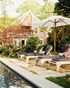 love this garden around the pool | Furniture Photo - A gathering of chaises and a white umbrella beside a pool | Lonny