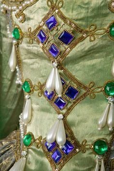 """This costume is from La Danse.  The V says : """" Green and gold silk Brocade, Bodice and Train lined with shot green silk, trimmed with gold Lace, Jewels of Sapphires, Emralds (sic), Pearls, Gold Tassels, Blue Ninon Scarf printed in gold design. Headdress of Pearls with Feather Mount, Lace Sleeves, Necklace. Sundries, Skirt and Bodice embroidered and jewelled. £35.10.0' (about £2,400 today, in 1910 £35 would have paid a craftsman builder for 107 days' work)."""