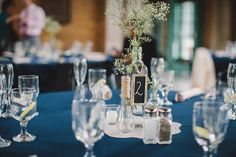 navy blue table linens with lace doily, baby's breath, glass bottle centerpiece and mini chalkboard for table number