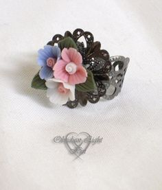 A beautiful trio of porcelain flowers atop gunmetal filigree make for a statement ring. Blossoms RIng. $18.00, via Etsy.