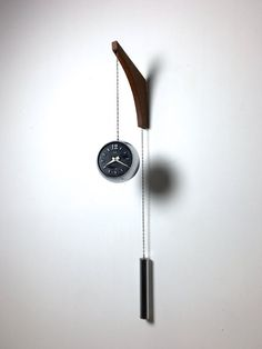 Crazy rare wall mounted clock with counterweight by Elgin, Germany 1950s. Chrome orb clock with black face and white enameled metal hands, strung