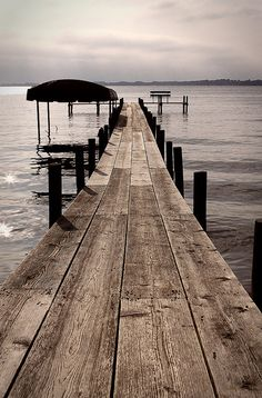 old wooden dock leading into a lake