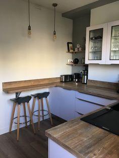 """Une petite cuisine d'une grande élégance aménagée par le magasin Arthur Bonnet de Toulouse - Portet-sur-Garonne. Ses façades blanches et son plan de travail en bois donnent à cet espace un caractère moderne et authentique. Les  tabourets hauts, les vitrines ainsi que les ampoules dénudées font un clin d'oeil aux cuisines de style """"bistrot""""."""