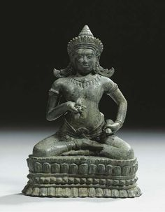 a khmer, bayon style, bronze figure of vajrasattva 13th century Seated in sattvasana on a lotus base, his hands holding the vajra and ghanta, wearing sampot, bejewelled, his face with serene expression, tiara in front of a conical-shaped headdress and elaborate ornaments, fine green patina 16.5 cm high