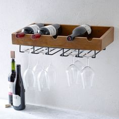 """Made of richly-grained mango wood, our Rustic Wine Shelf holds bottles up top and glasses down below. 21.5""""w x 10""""d x 6""""h. Mango wood body. Aluminum glass racks. Hanging hardware included. Made in India."""