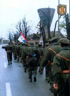 The Serbian Volunteer Guard march past the Vukovar water tower.