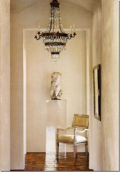 This entry hall is stunningly beautiful – simple yet elegant. A headless sculpture on a Plexiglas stand is the eye candy at the end of the view. An antique chair grounds the vignette. But, the chandelier is the jewelry here. The French empire antique could not be more perfect – hard to imagine this entry hall with the chandelier. Design by Renea Abbott.